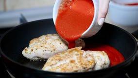 μαγείρεμα κοτόπουλου Χύστε τη σάλτσα ντοματών στο κοτόπουλο απόθεμα βίντεο