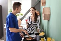 Μαγείρεμα νεαρών άνδρων με τη φίλη στην κουζίνα στοκ φωτογραφία