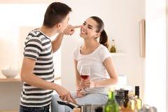 Μαγείρεμα νεαρών άνδρων με τη φίλη στην κουζίνα στοκ εικόνες