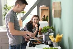 Μαγείρεμα νεαρών άνδρων με τη φίλη στην κουζίνα στοκ εικόνα με δικαίωμα ελεύθερης χρήσης