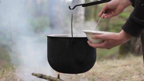 Μαγείρεμα σε ένα δοχείο πέρα από την πυρά προσκόπων απόθεμα βίντεο