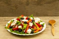 Μαγείρεμα της θερινής ελληνικής σαλάτας στο ξύλινο υπόβαθρο Στοκ φωτογραφία με δικαίωμα ελεύθερης χρήσης