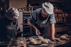 Μαγείρεμα της κύριας κατηγορίας στο αρτοποιείο Αρχιμάγειρας με το βοηθό του που παρουσιάζει έτοιμα δείγματα της δοκιμής ψησίματος στοκ φωτογραφία