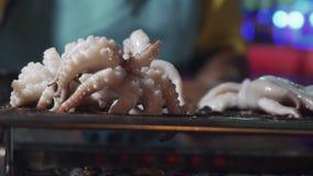 Μαγείρεμα του χταποδιού στη σχάρα στην ασιατική αγορά νύχτας Τοπικός προμηθευτής που προετοιμάζει bbq θαλασσινών Τρόφιμα οδών για απόθεμα βίντεο