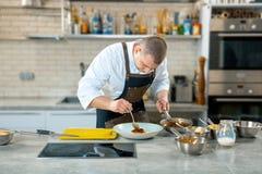 Μαγείρεμα τροφίμων, επάγγελμα και έννοια ανθρώπων - αρσενικό εξυπηρετώντας πιάτο μαγείρων αρχιμαγείρων των γλωσσών polenta και μο στοκ φωτογραφία