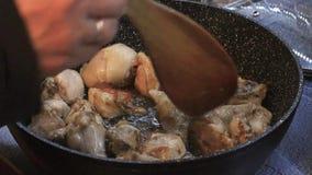 Μαγείρεμα των κομματιών κοτόπουλου σε ένα τηγανίζοντας τηγάνι απόθεμα βίντεο