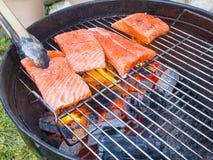 Μαγείρεμα των φρέσκων μπριζολών σολομών στη σχάρα, υπαίθρια το καλοκαίρι στοκ εικόνα με δικαίωμα ελεύθερης χρήσης