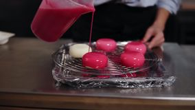 Μαγείρεμα, ψήσιμο και έννοια επιδορπίων Κλείστε επάνω των χεριών γυναικών κρατώντας το χύνοντας λούστρο κανατών στα κέικ στο δίσκ φιλμ μικρού μήκους
