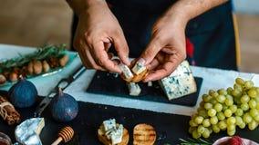 Μαγείρεμα Bruschettas με τα σύκα, το μπλε τυρί και τα ξύλα καρυδιάς στο ψημένο στη σχάρα φλοιώδες ψωμί από τα χέρια αρχιμαγείρων  στοκ εικόνες με δικαίωμα ελεύθερης χρήσης