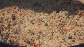 Μαγείρεμα pilaf στο καζάνι και μίξη pilaf του κουταλιού κουζινών εκμετάλλευσης Ασιατικό παραδοσιακό μαγειρικό πιάτο - pilaf απόθεμα βίντεο