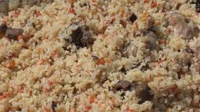Μαγείρεμα pilaf στο καζάνι και μίξη pilaf του κουταλιού κουζινών εκμετάλλευσης φιλμ μικρού μήκους