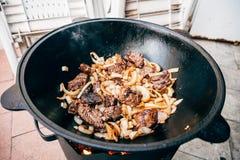 Μαγείρεμα plov στο καζάνι Μόνο κρέας και κρεμμύδια σε ένα καζάνι Στοκ Φωτογραφία