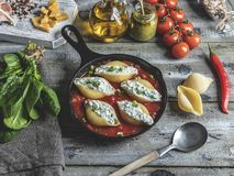 Μαγειρευμένα γεμισμένα σπανάκι ζυμαρικών conchiglioni και τυρί, σάλτσα ντοματών στοκ φωτογραφία με δικαίωμα ελεύθερης χρήσης