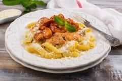 Μαγειρευμένα ιταλικά ζυμαρικά με τη σάλτσα κοτόπουλου και ντοματών Στοκ Φωτογραφία