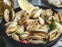 Μαγειρευμένα μαλάκια θαλασσινών στην παν μερίδα σιδήρου με το λεμόνι και το καρύκευμα στοκ φωτογραφία με δικαίωμα ελεύθερης χρήσης