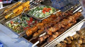 Μαγειρευμένα τρόφιμα οδών στο μετρητή καταστημάτων Shish kebabs στα οβελίδια, ψημένα στη σχάρα μανιτάρια, λαχανικά απόθεμα βίντεο