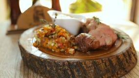 Μαγειρευμένος πάσσαλος με τη σάλτσα στο ξύλινο πιάτο απόθεμα βίντεο