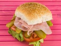 Μαγειρευμένο καπνισμένο ζαμπόν με το ρόλο ψωμιού σπόρου σουσαμιού σαλάτας αγγουριών ή το σάντουιτς κουλουριών Στοκ φωτογραφία με δικαίωμα ελεύθερης χρήσης