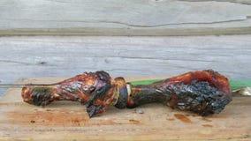 Μαγειρευμένο κρέας σε μια σχάρα σε έναν ξύλινο πίνακα με τα πράσινα κρεμμύδια Κατακόκκινα, ελαφρώς μμένα κομμάτια Ξύλινος τοίχος φιλμ μικρού μήκους