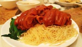 Μαγειρευμένο νουντλς αυγών που εξυπηρετείται με τα μεγάλα πόδια χοιρινού κρέατος στο άσπρο πιάτο, κινεζικό ύφος Στοκ φωτογραφία με δικαίωμα ελεύθερης χρήσης