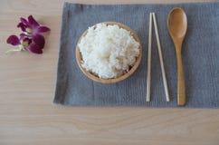 Μαγειρευμένο ρύζι σε ένα ξύλινο κύπελλο και κουτάλι, chopsticks σε ένα ξύλινο υπόβαθρο Στοκ Εικόνες