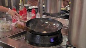 Μαγειρεύει την προετοιμασία των τροφίμων στη σόμπα που τηγανίζει wok με την πυρκαγιά στη μεγάλη σύγχρονη κουζίνα εστιατορίων απόθεμα βίντεο