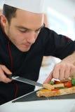 Μαγειρεύοντας αρχιμάγειρας που προετοιμάζει έναν εκκινητή Στοκ Φωτογραφίες