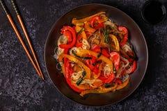 Μαγειρεύοντας Ασιάτης ανακατώνει τα νουντλς τηγανητών με τα λαχανικά Στοκ Εικόνα
