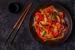 Μαγειρεύοντας Ασιάτης ανακατώνει τα νουντλς τηγανητών με τα λαχανικά Στοκ Φωτογραφίες