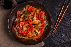 Μαγειρεύοντας Ασιάτης ανακατώνει τα νουντλς τηγανητών με τα λαχανικά Στοκ Εικόνες