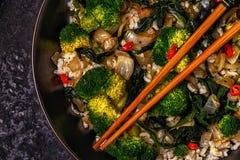 Μαγειρεύοντας Ασιάτης ανακατώνει το ρύζι τηγανητών με τα λαχανικά Στοκ εικόνα με δικαίωμα ελεύθερης χρήσης