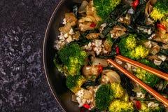 Μαγειρεύοντας Ασιάτης ανακατώνει το ρύζι τηγανητών με τα λαχανικά Στοκ Εικόνες