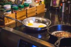 Μαγειρεύοντας αυγά με το πρόγευμα Στοκ Φωτογραφίες