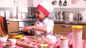 Μαγειρεύοντας βάφλες μικρών κοριτσιών στην κουζίνα φιλμ μικρού μήκους
