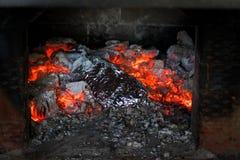 Μαγειρεύοντας γεύμα στους ζωντανούς άνθρακες μέσα στη ρωσική σόμπα Αγροτικά αυθεντικά τρόφιμα Ψημένα τρόφιμα στο foi στοκ φωτογραφία