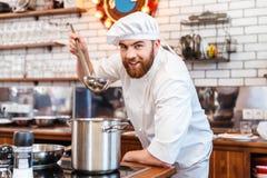 Μαγειρεύοντας και δοκιμάζοντας σούπα μαγείρων αρχιμαγείρων από το τηγάνι που χρησιμοποιεί την κουτάλα Στοκ Εικόνες
