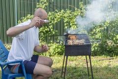 Μαγειρεύοντας κρέας ατόμων στη σχάρα Νέο ζεύγος που κάνει τη σχάρα στον κήπο τους Μαγειρεύοντας κρέας ατόμων στη σχάρα Στοκ Εικόνα