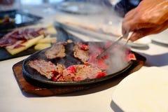 Μαγειρεύοντας κρέας ευθεία ο πελάτης υπολογιστών γραφείου στο καυτό φύλλο ψησίματος πυκνά Εστιατόριο EL Meson de Λα Costa Torrevi Στοκ Φωτογραφίες