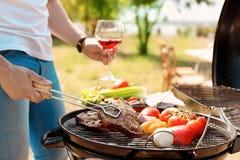 Μαγειρεύοντας κρέας και λαχανικά ατόμων στη σχάρα σχαρών υπαίθρια Στοκ Εικόνες