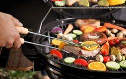 Μαγειρεύοντας κρέας και λαχανικά ατόμων στη σχάρα σχαρών, κινηματογράφηση σε πρώτο πλάνο Στοκ Φωτογραφία