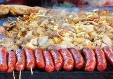 Μαγειρεύοντας κρέας, λαχανικά και λουκάνικα σε ένα ταψάκι Στοκ Εικόνες