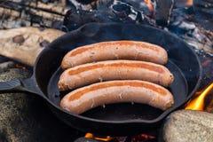 Μαγειρεύοντας λουκάνικα στο skillet χυτοσιδήρου στην πυρά προσκόπων στρατοπεδεύοντας Καλά και θετικά τρόφιμα πυρών προσκόπων Στοκ Εικόνα