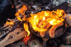 Μαγειρεύοντας λουκάνικα στο skillet χυτοσιδήρου στην πυρά προσκόπων στρατοπεδεύοντας Καλά και θετικά τρόφιμα πυρών προσκόπων Στοκ φωτογραφίες με δικαίωμα ελεύθερης χρήσης