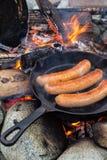 Μαγειρεύοντας λουκάνικα στο skillet χυτοσιδήρου στην πυρά προσκόπων στρατοπεδεύοντας Καλά και θετικά τρόφιμα πυρών προσκόπων Στοκ Εικόνες