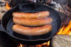 Μαγειρεύοντας λουκάνικα στο skillet χυτοσιδήρου στην πυρά προσκόπων στρατοπεδεύοντας Καλά και θετικά τρόφιμα πυρών προσκόπων Στοκ Φωτογραφίες