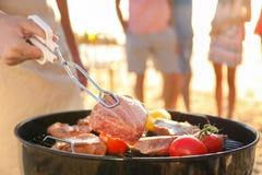 Μαγειρεύοντας μπριζόλες και λαχανικά ατόμων στη σχάρα σχαρών Στοκ εικόνα με δικαίωμα ελεύθερης χρήσης