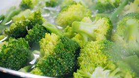 Μαγειρεύοντας μπρόκολο και πράσινα φασόλια σε ένα τηγανίζοντας τηγάνι κλείστε επάνω απόθεμα βίντεο
