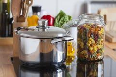 Μαγειρεύοντας δοχείο και ένα βάζο αποθήκευσης με τα ζωηρόχρωμα ζυμαρικά Στοκ φωτογραφίες με δικαίωμα ελεύθερης χρήσης