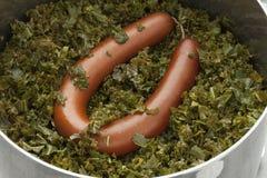 Μαγειρεύοντας δοχείο με το μαγειρευμένα σγουρό κατσαρό λάχανο και το λουκάνικο Στοκ Εικόνα