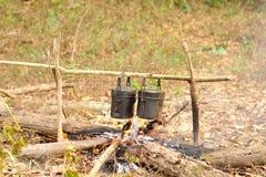 Μαγειρεύοντας δοχείο στην πυρά προσκόπων, που στρατοπεδεύει στο δάσος Στοκ Εικόνα